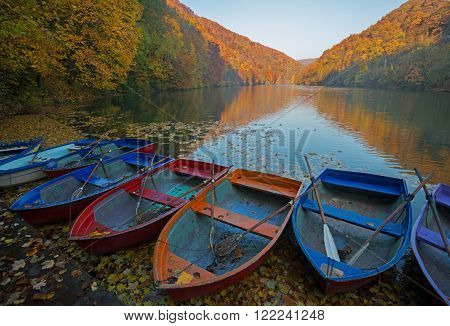 Lillafured is a popular tourist resort in Bukk Mountains (Hungary). Yellow hills reflect in lake. Multicolored boat for rent in foreground.