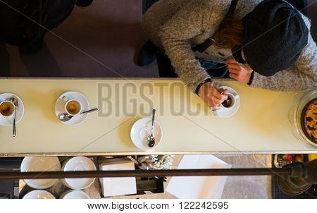 Woman customer drinking italian espresso coffee at bar counter in coffee shop