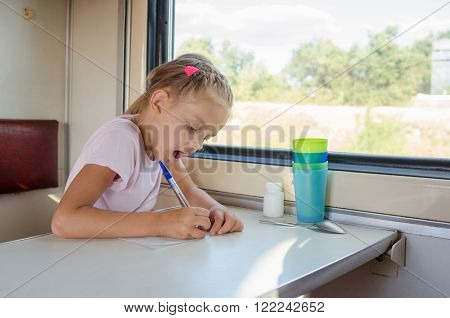 Girl Draws A Pen On A Sheet Of Paper In A Second-class Train Carriage