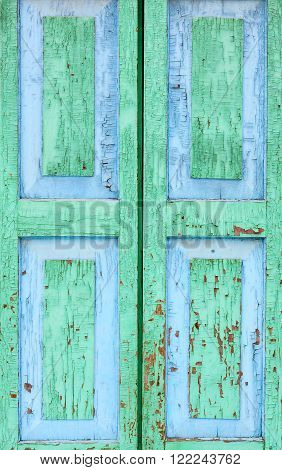 Detail of an old window. Peeling paint green and blue color on the wooden shutters. The texture of old wood as background. Country style.