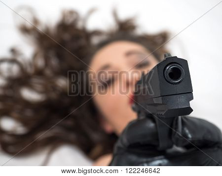 girl lying pointing a gun focus on the gun