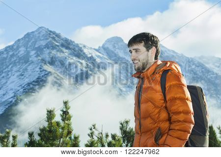 Cheerful mountain guide is having rest at astonishing winter rocky landscape background
