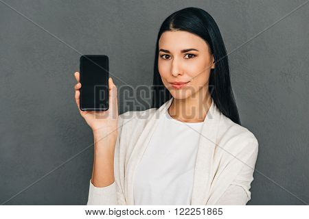 Take a look here! Beautiful young woman shoving smartphone with copy space and looking at camera while standing against grey background
