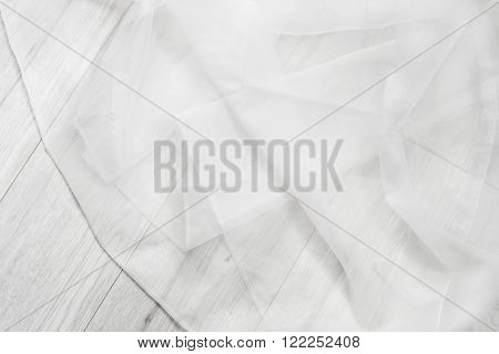White folded tulle on white wooden background