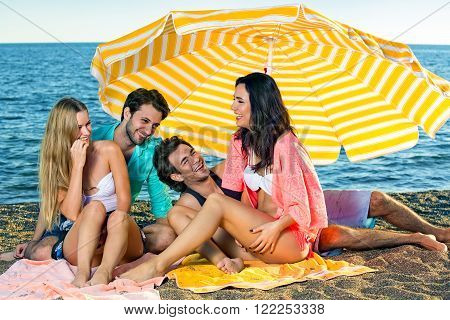 Two young couples enjoying vacation at the beach.