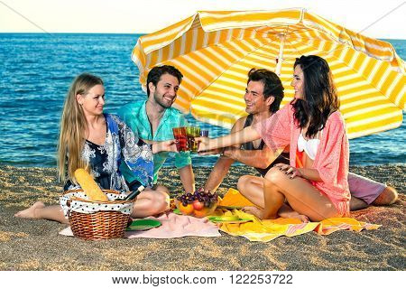 Four happy friends have a picnic on the beach. Four smiling friends wearing swimsuits toast on the beach under a striped yellow umbrella sharing fruit bread and wine.