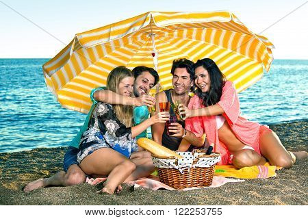 Vacationing friends toast on the beach near a wicker picnic basket holding bread and wine while wearing swimsuits