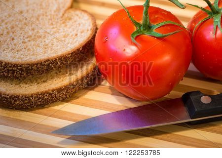 Vine ripened  and tomatoes on the cutting board with bread and a knife