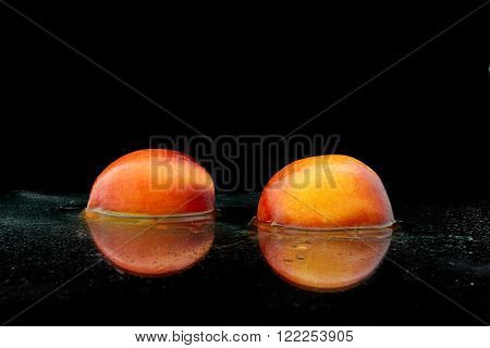 a divided peach with water on black background