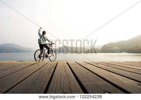 Young woman biking on pier looking natural lake with fist on air.