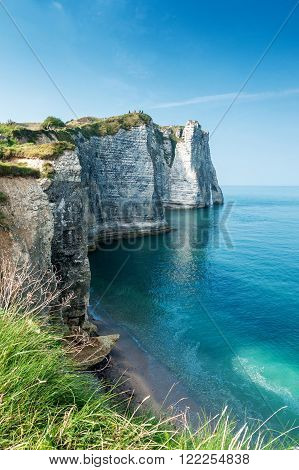 The white cliffs of Etretat overlooking the famous Natural Arch La Porte d`Aval, in the foreground small wooden boats, Alabaster Coast, Normandy, France ** Note: Visible grain at 100%, best at smaller sizes