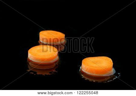 three slices carrot with water on black background