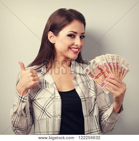 Happy Young Casual Woman In Glasses Holding Roubles And Showing Thumb Up Sign With Toothy Smiling. T