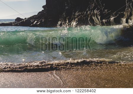 Big wave luminescent in sunlight coming to the beach cliffs on background