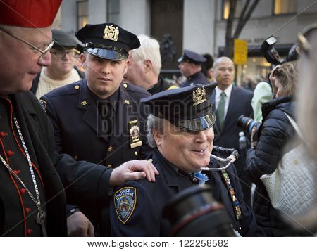 NEW YORK - MARCH 17, 2016: Timothy Cardinal Dolan Archbishop of New York greets NYPD Det. Steven McDonald and his son NYPD Det. Conor McDonald in front of St Patricks Cathedral on Saint Patricks Day.