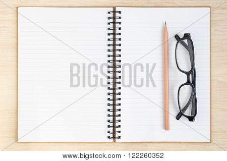 Open spiral notebook empty line paper with brown pencil and black glasses - notebook paper on wood background - working desk top view