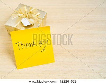 Hand writing - Thank you - words on yellow sticky note with gold gift box on wood background