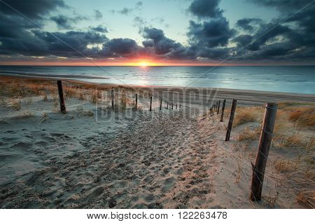 sand path to North sea beach at sunset Netherlands