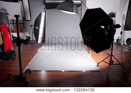 Empty photo studio with lighting equipment, Dark studio with grey background