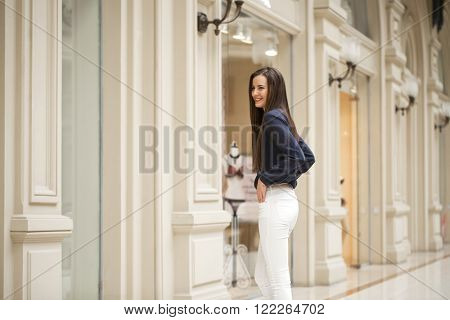 Fashion portrait of young brunette model posing in shop. Young woman in blue shirt and white pants