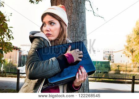 scared woman trying to protect her laptop pc and data looking helpless and vulnerable - privacy and identity theft concept