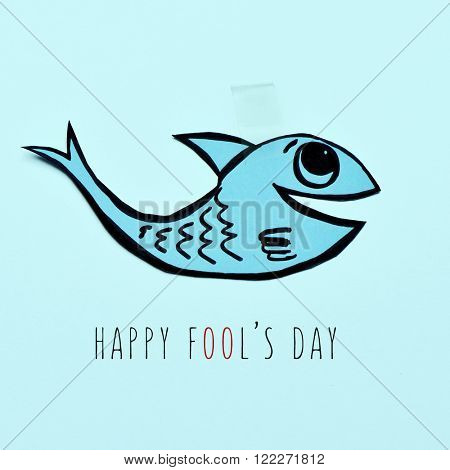 a handmade paper fish attached with adhesive tape and the text happy fools day on a blue background