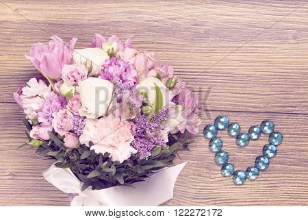 Valentine flowers on with heartshaped jewellery wooden background