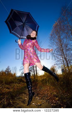 young beautiful smiling woman jump outdoor with umbrella in hand
