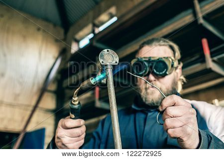 Man with goggles soldering an iron pipe