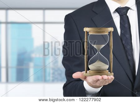Businessman holding sand glass on palm. Sand running. Blurred office at background. Concept of time.