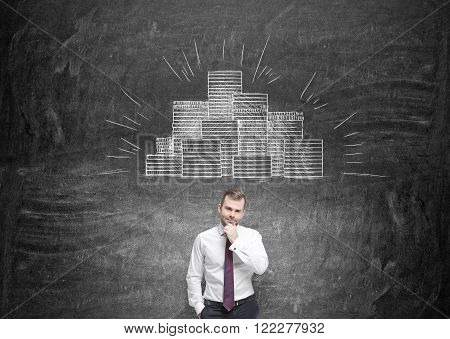 Businessman with hand to chin picture of coin piles drawn over his head. Black background. Concept of making money.