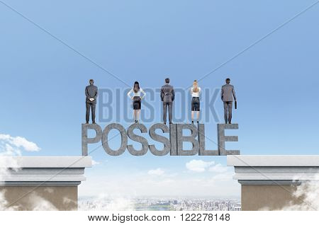 Businessmen and businesswomen standing on letters bridging two roofs. Blue sky and city at background. Concept of possibility.