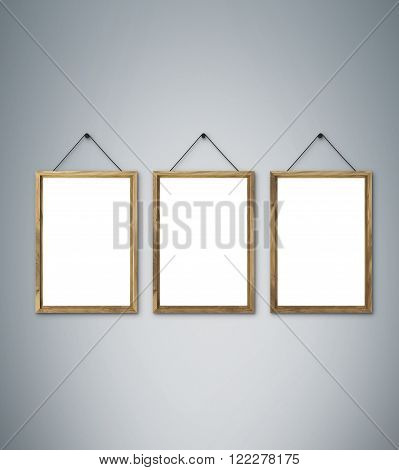 Three blank wooden frames on nails. Grey background. Concept of picture on wall. Mock up. 3D render