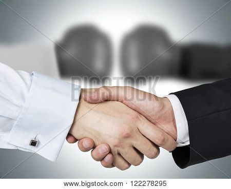 Two shaking hands two blurred hands in boxer gloves at background. Concept of double game.