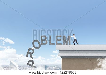 Businessman pushing letters of word 'problem' from roof. Blue sky and Paris at background. Concept of coping with problem.