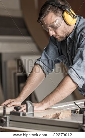 Carpenter is cutting wooden plank in his workshop