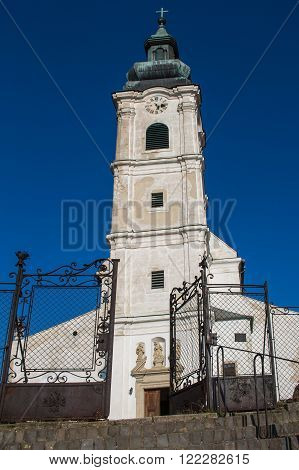 Entrance to the Church of Saint Cross. Old facade high tower with clock. Cross on the tower. Bright blue sky.