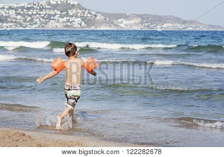 The boy runs to the sea with armbands for swimming. Safety of children on the beach.