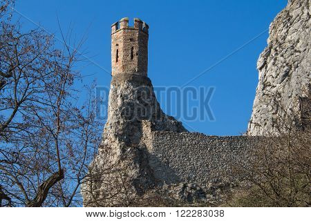 Rocks of the former fortress with a Maiden Tower part of ruins of castle Devin in Slovakia. Bright blue sky.