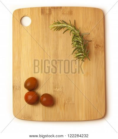 A branch of rosemary and three cherry tomatoes forming a frame for your text on a wooden board on white background