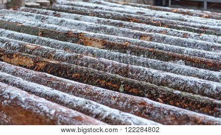 Image of many snow-covered logs at sawmill