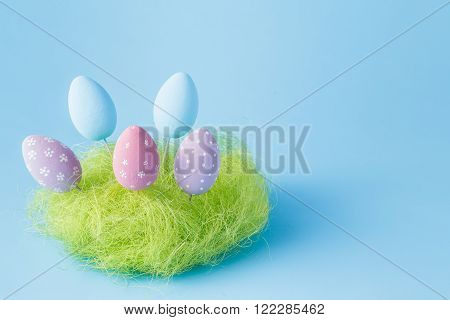 Easter composition on blue background with nest