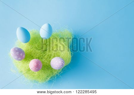 Springtime nest with colorful Easter Eggs against blue background