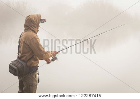 Autumn fishing. Fisherman in his hand holding spinning. Fishing, spinning reel, fish, Breg rivers. - The concept of a rural getaway. Article about fishing.