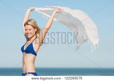Beautiful young woman wearing blue bikini with flying scarf on beach. Carefree young woman on seaside looking at camera. Smiling girl on beach holding white scarf fluttering in the wind.