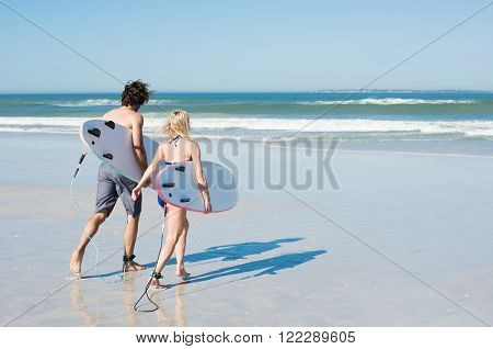 Couple running with their surfboard on the beach. Surfers carrying their surfboards while going to the sea. Rear view of couple with surfboards running to the sea.
