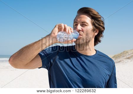 Young man drinking water after workout at beach. Handsome man resting at beach on a summer morning after run. Daily routine workout of a man.