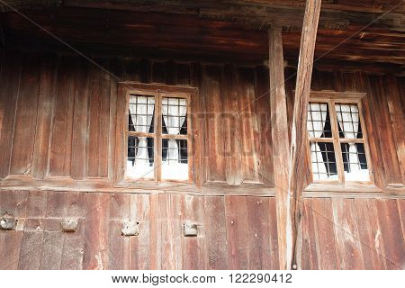Windows of the old wooden log house on the background of wooden walls
