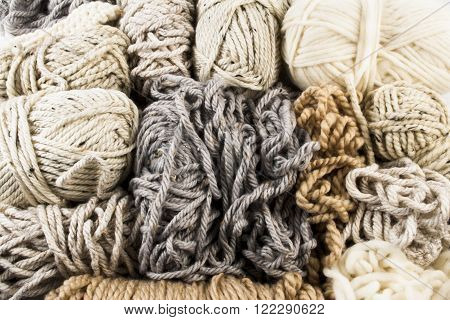 Messy yarn skeins and scraps in white beige gray and light brown colors