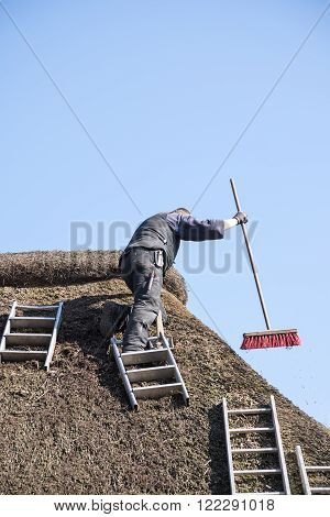 roofer with ladders on a thatched roof to remove moss and dirt with a broom blue sky with copy space